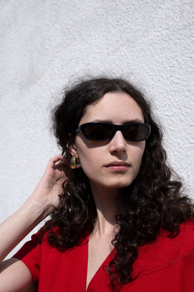 Rosalind Jana wears gold dimpled curved earrings with black wraparound shades and a red peplum jacket by Human Sea Vintage