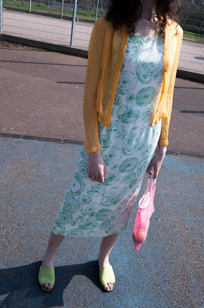 Rosalind Jana wears silk tie-dye maxi dress, sheer orange silk Just Cavalli blouse and pink mesh market bag for Human Sea Vintage
