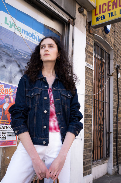 Rosalind Jana wears United Colours of Benetton denim jacket, gingham tank top and white Escada jeans for Human Sea Vintage