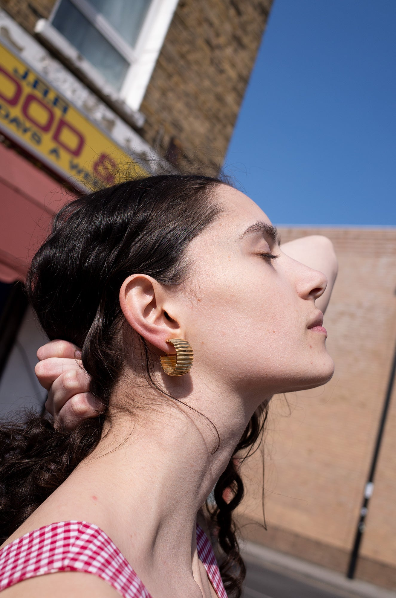 Rosalind Jana wears gold crinkle hoop earrings with red gingham top for Human Sea Vintage