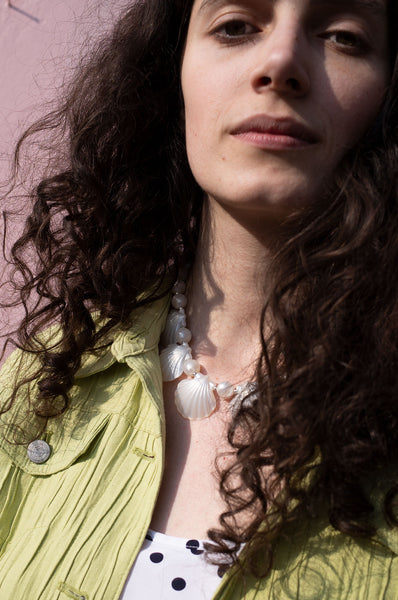 Rosalind Jana wears shell necklace and lime-green jacket for Human Sea Vintage