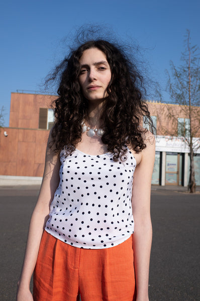 Rosalind Jana wears white polka-dot camisole and orange trousers for Human Sea Vintage