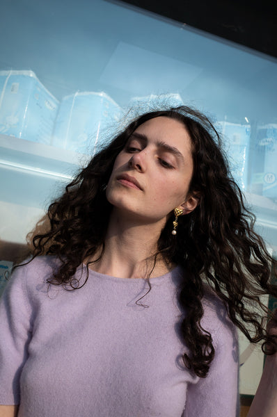 Rosalind Jana wears gold heart-shaped drop earrings and lilac cashmere short-sleeve jumper for Human Sea Vintage