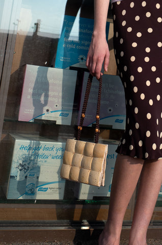 Rosalind Jana wears brown polka dot slip skirt and coconut shell bag by Human Sea Vintage