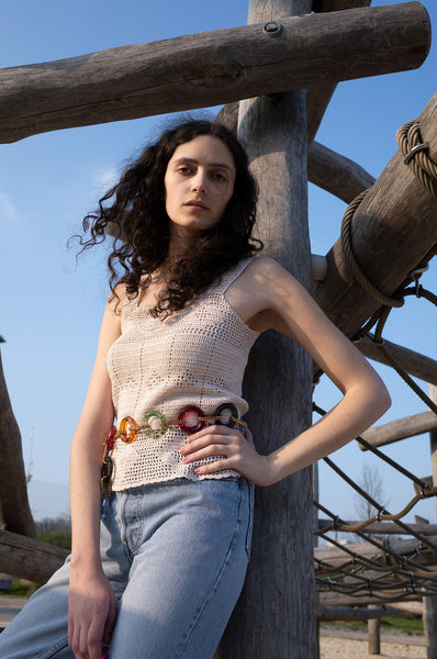 Rosalind Jana wears multi-coloured lucite chain belt, crochet tank top and Levis jeans for Human Sea Vintage