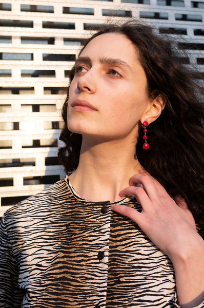 Rosalind Jana wears magenta beaded drop earrings and tiger-stripe cardigan by Human Sea Vintage