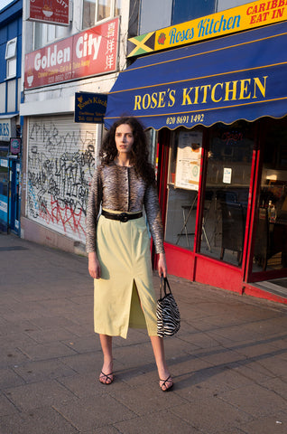 Rosalind Jana wears animal print bag, cardigan and lime-green midi skirt by Human Sea Vintage