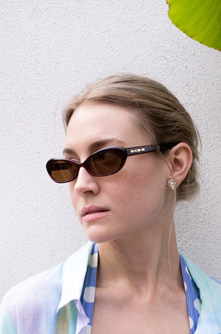 Model wears vintage 1990s Katharine Hamnett tortoiseshell cat eye sunglasses