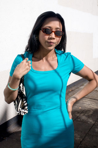 Model wears vintage 1990s sunglasses with blue Moschino Jeans dress