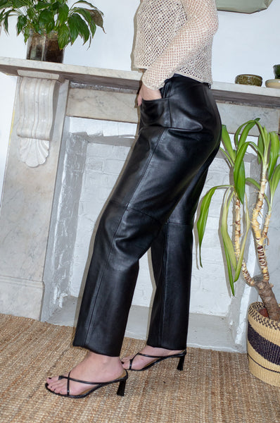 Model wears vintage black leather tapered trousers by Human Sea Vintage