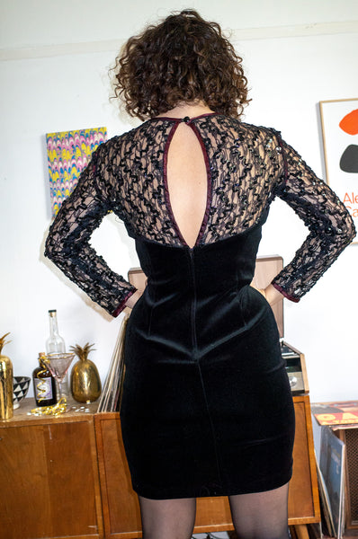 Model wears black sequined velvet dress by Human Sea Vintage