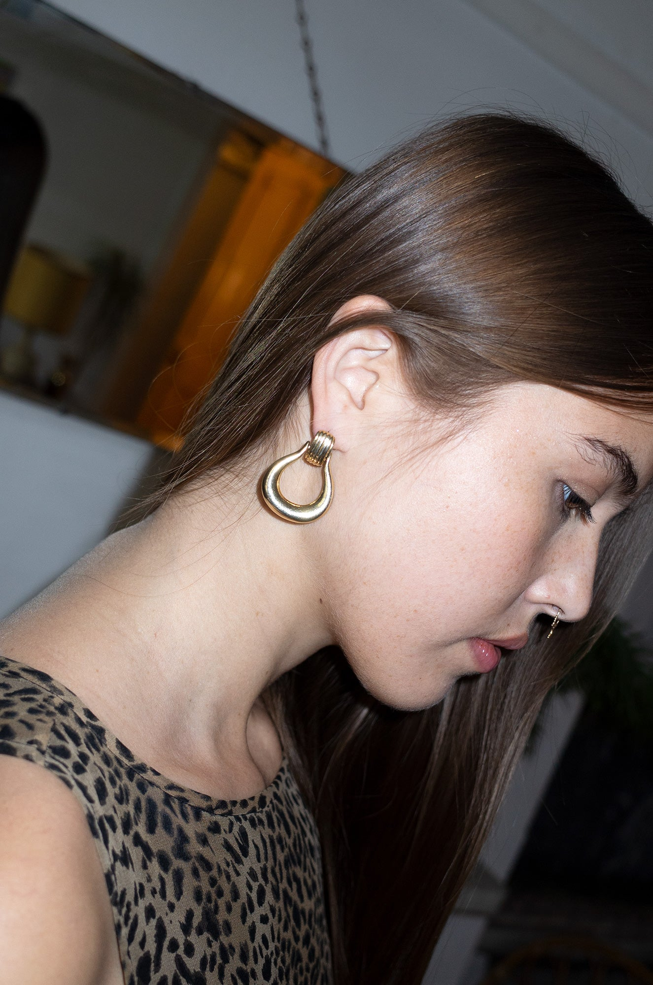Model wears oversized gold door knocker earrings