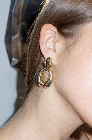 Model wears vintage gold oversized statement earrings