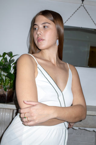 Model wears mother-of-pearl reverse teardrop earrings with a white vintage cocktail dress