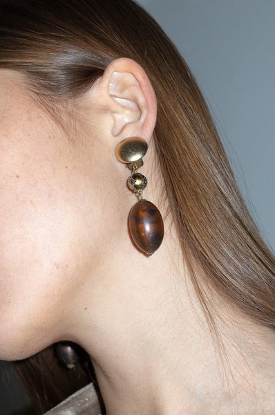 Model wears amber resin drop earrings with clip-on fastening