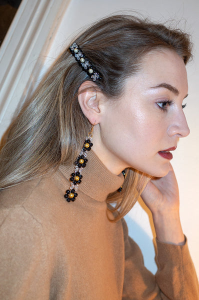 Model wears four tier daisy earrings by Blóma x Human Sea