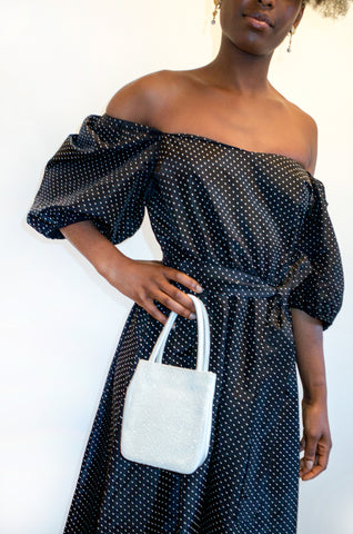 Model wears black puff sleeve dress while holding white leather and glitter handbag