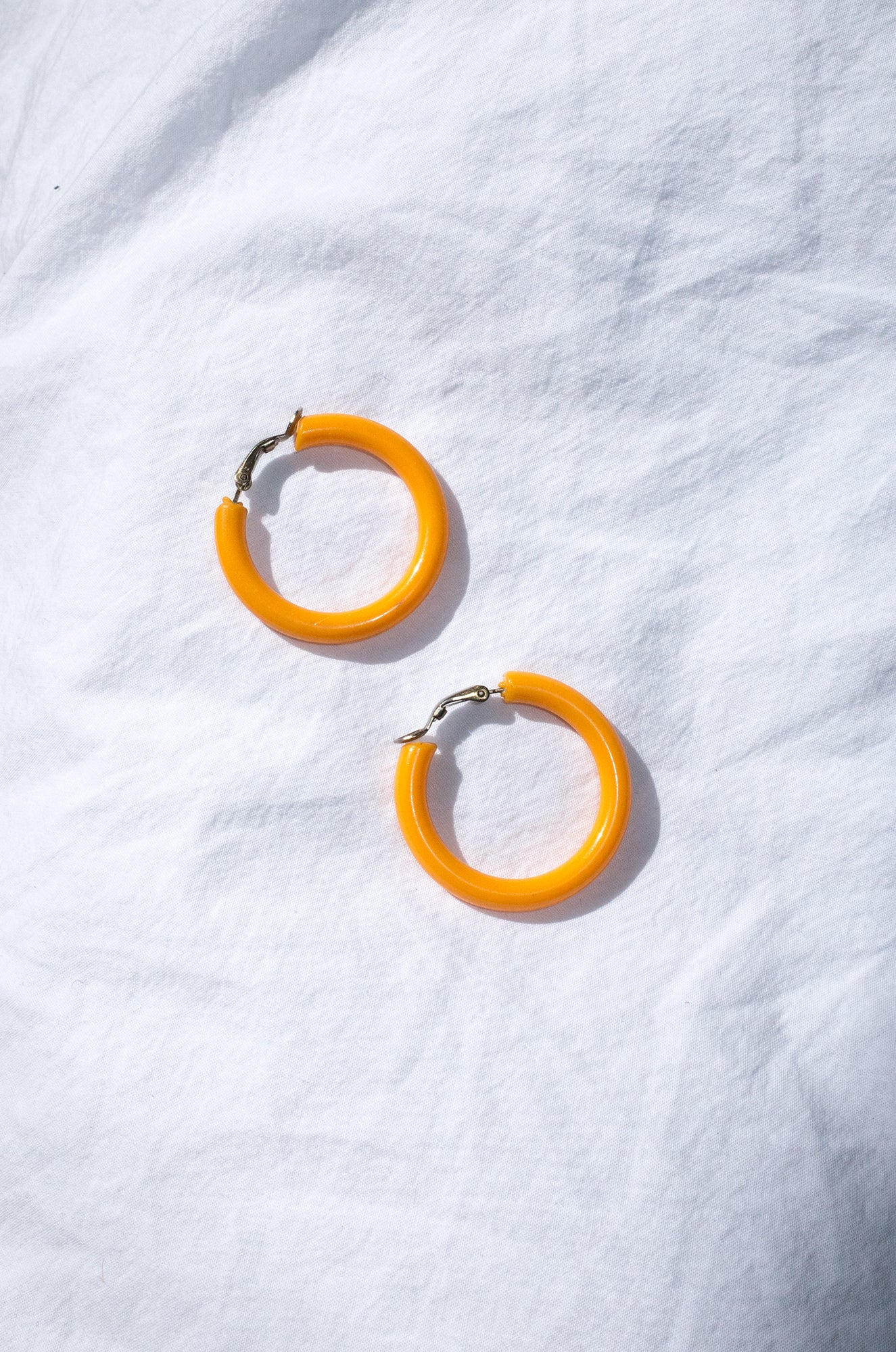 Vintage 1960s tangerine plastic hoop earrings