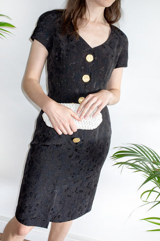 A vintage 1980s black fitted formal dress with scalloped detailing at front and oversized gold buttons