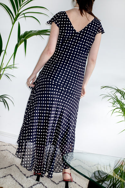 An vintage Y2K black and white polka-dot midi dress with capped sleeves and asymmetric skirt