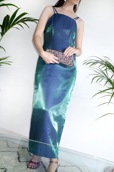 Woman wearing a shimmering Y2K vintage petrol-green sleeveless evening dress