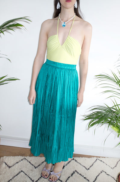 Model wears lime-green swimsuit, turquoise silk crinkle skirt and a glass pendant necklace.