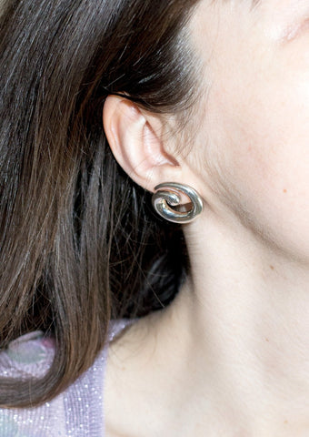 Woman wearing silver spiral stud earrings