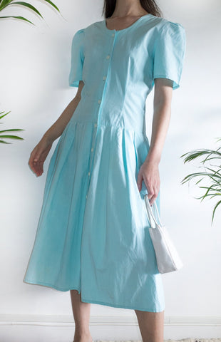 Woman wearing a vintage aqua-blue cotton day dress from the 1980s.