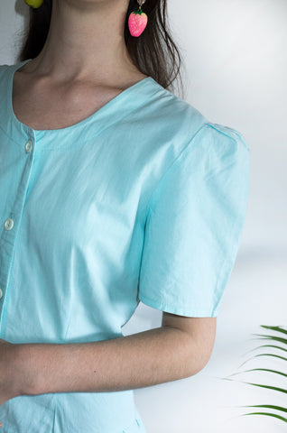 Close up on the sleeve detail of a vintage aqua-blue cotton day dress from the 1980s.
