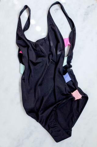 A vintage 1990s black one-piece swimsuit with pastel detailing at the sides