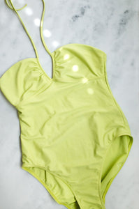A vintage Y2K acid green one-piece swimsuit with halter-neck straps
