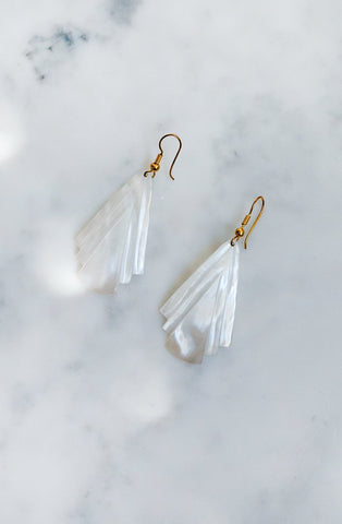 Mother-of-pearl shell earrings with engraved geometric design and gold-tone wire fastening.