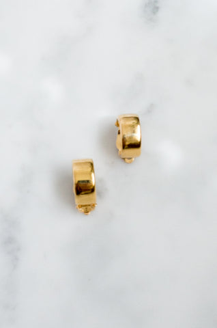 A pair of gleaming gold-tone clip-on vintage hoop earrings.