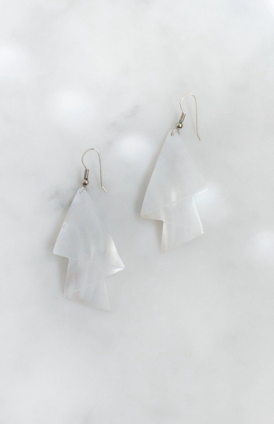 Mother-of-pearl shell earrings with engraved zigzag design and silver-tone wire fastening.