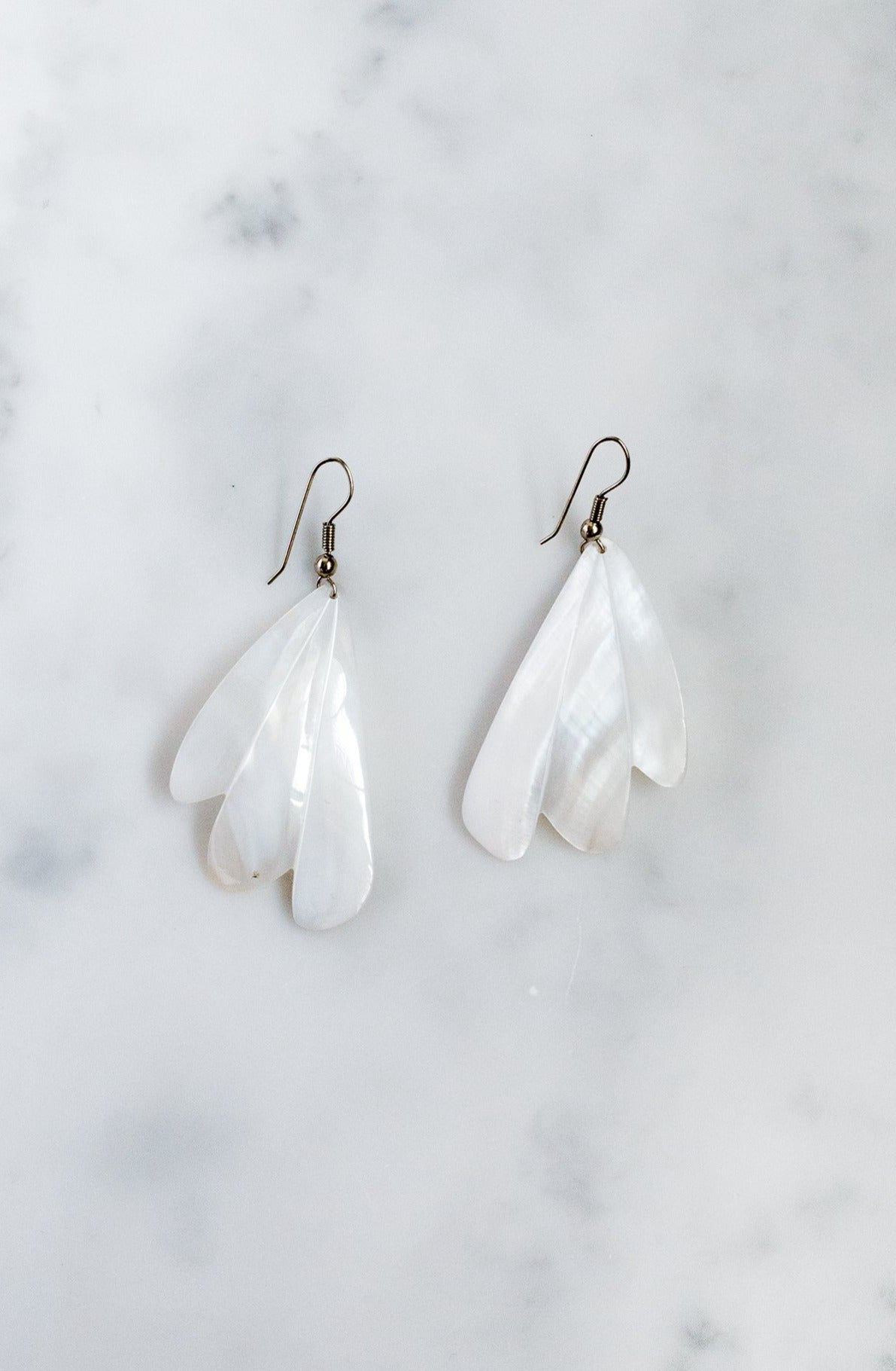 Mother-of-pearl shell earrings with engraved wing-shaped design and silver-tone wire fastening.