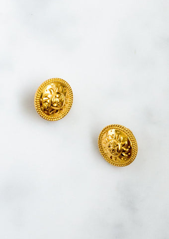 Gold-plated medallion earrings with embossed sun face and clip-on fastening.