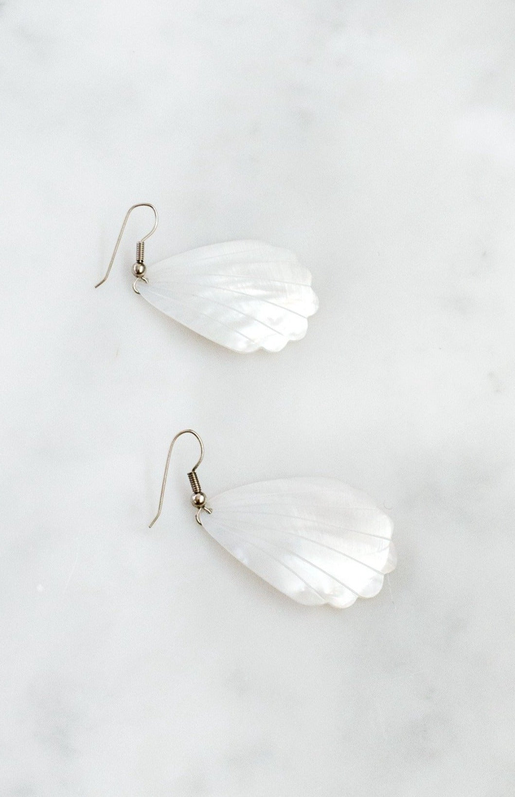 Mother-of-pearl shell earrings with engraved scalloped-edge design and silver-tone wire fastening.