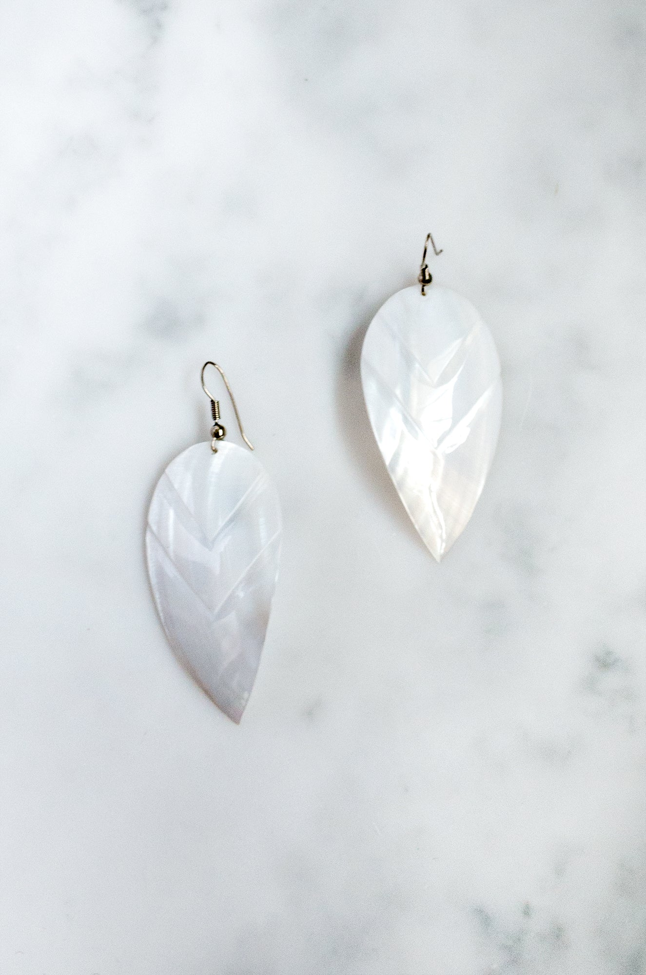 Mother-of-pearl shell earrings with engraved leaf-shaped design and silver-tone wire fastening.
