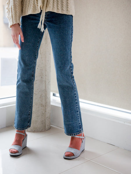 Woman wearing vintage early 1990s designer blue denim straight-leg jeans.
