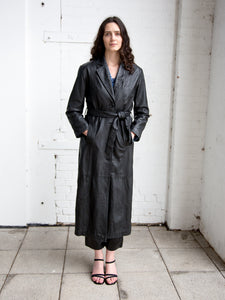 Woman wearing vintage 1990s black full-length single-breasted trench coat