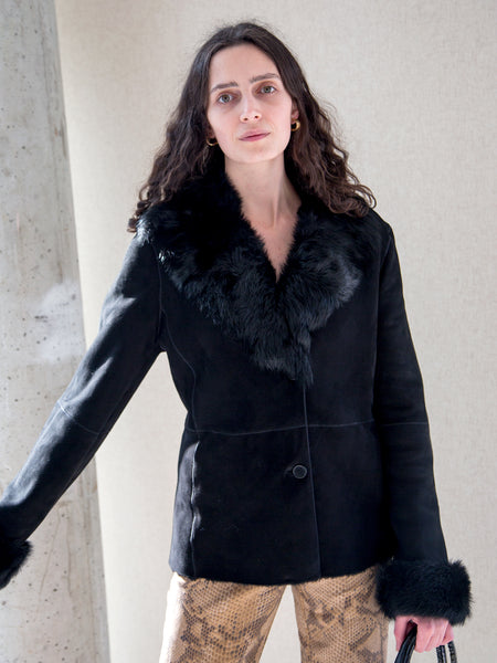 Woman wearing luxurious vintage Y2K black Toscana jacket with oversized fur collar and cuffs