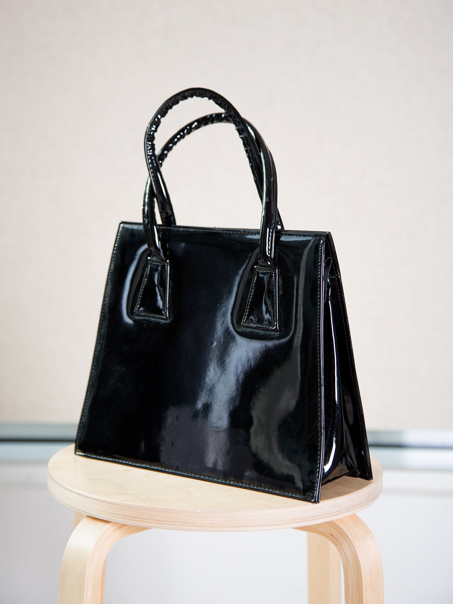 A vintage 1970s black patent top-handle bag