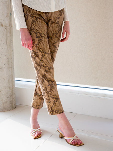 Woman wearing snake-print jeans with gold sequinned minimalist mules
