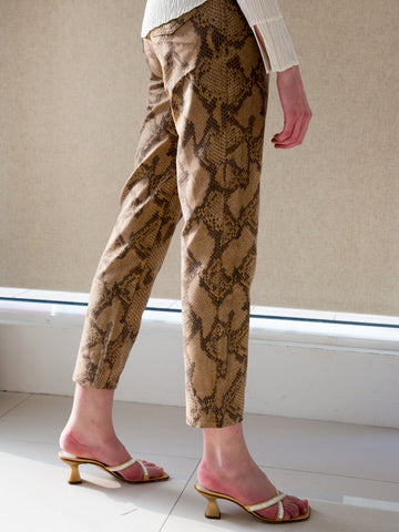 Woman wearing vintage 1990s designer snake-print high-waisted mom jeans