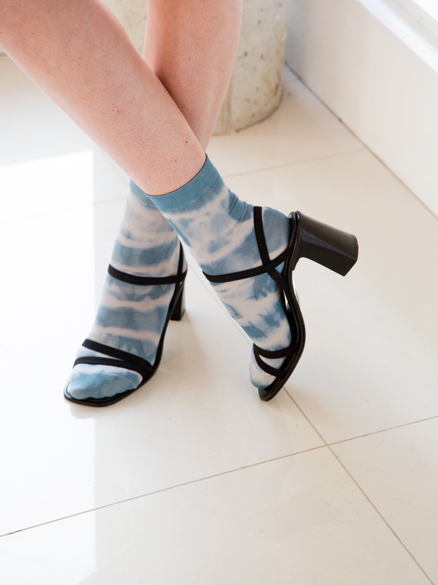 Woman wearing naturally-dyed silk socks with black strappy sandals