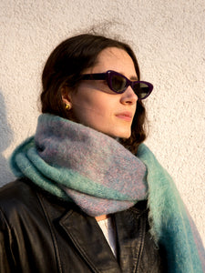Woman wearing vintage 1960s purple narrow cat-eye sunglasses.