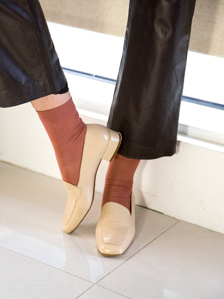 Woman wearing naturally-dyed silk socks with cream leather loafers
