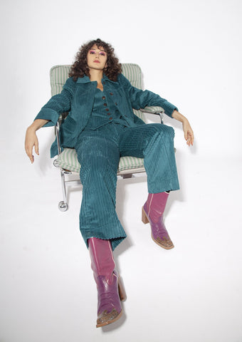 Woman wearing teal cord suit and pink cowboy boots
