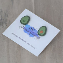 Avocado stud earrings by Heartbeat Handicrafts on card over timber flooring