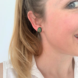 Avocado stud earrings by Heartbeat Handicrafts being worn on model's ear